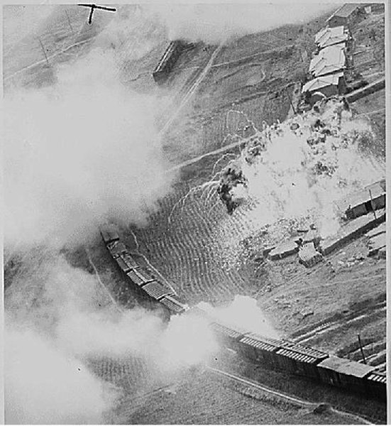 The tank of napalm dropped by Fifth Air Force B-26 Invader light bombers of the 452nd Bomb Wing (light) on this Red marshalling yard at Masen-ni, North Korea, has blended with a stockpile of supplies on a loading platform to from a fiery inferno, ca. 07/11/1951