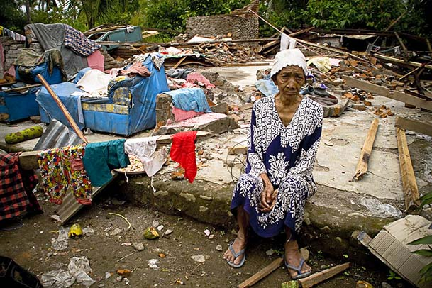 An old ibu (woman) sits among the ruins of her house in Pariaman, north of Padang, West Sumatra. Crédits image : US Department of Foreign Affairs and Trade