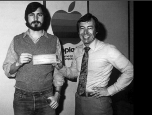 Steve Jobs and Mike Markkula with a cheque symbolising his investment in Apple, 1977. Source : allaboutstevejobs.com