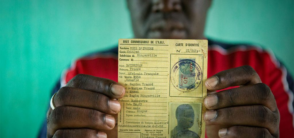Oumar, who was at risk of statelessness, holds his father's identity card from French colonial times. UNHCR/Hélène Caux