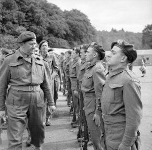 tenente colonnello Charles Vaughan, comandante commando deposito, ispezionando le truppe francesi durante una parata per segnare la Giornata della Bastiglia Achnacarry in Scozia, 17 luglio 1943. Crediti: collezioni dei musei della guerra imperiale.