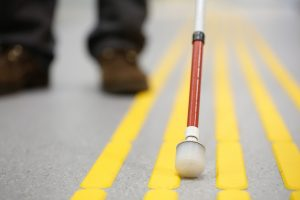 Blind pedestrian walking and detecting markings on tactile paving with textured ground surface indicators for blind and visually impaired. Blindness aid, visual impairment, independent life concept. De zlikovec. Shutterstock