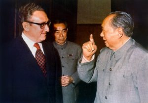 Henry Kissinger and Chairman Mao, with Zhou Enlai behind them in Beijing, early 70s. By Oliver Atkins (Jiang -original uploader on en wiki) [Public domain], via Wikimedia Commons