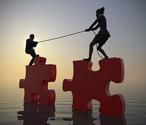 Team pulling giant jigsaw puzzle into position at sea at sunrise. Two executives pull giant jigsaw puzzle pieces into position at sunrise demonstrating teamwork at sea. Crédits : emerge, Shutterstock