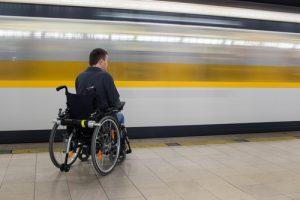 Le train passe devant une personne en fauteuil roulant. Crédits photo : Graceful Digital, Shutterstock