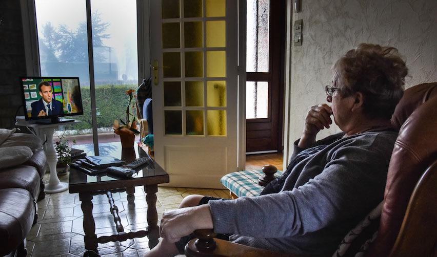 Femme regardant Emmanuel Macron à la télévision
