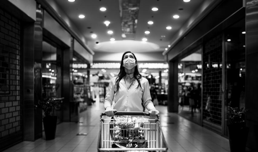 Woman wearing a mask pushing a shopping cart. © eldar nurkovic / Shutterstock